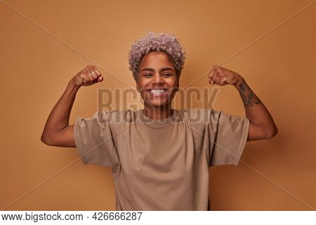 Strong Powerful African Woman Raises Arms And Shows Biceps Against Brown Wall