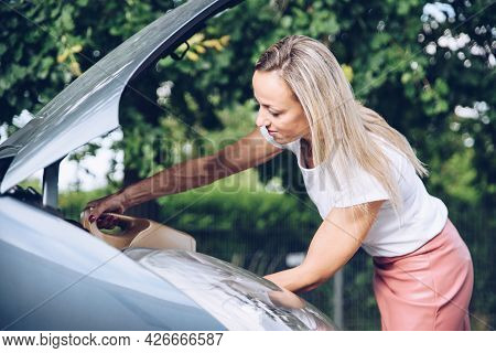 Woman Holding Can Of Engine Oil And Pouring It Through Funnel Into Car.