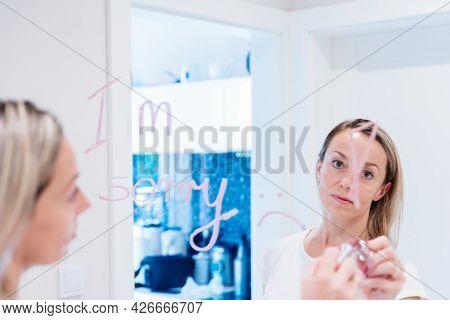Sad Woman Writes The Words Im Sorry On The Mirror.