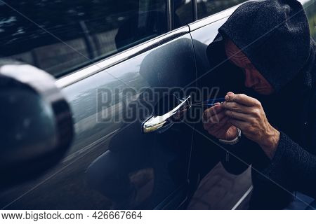 Thief Breaking Into Car With Picklock Or Screwdriver.