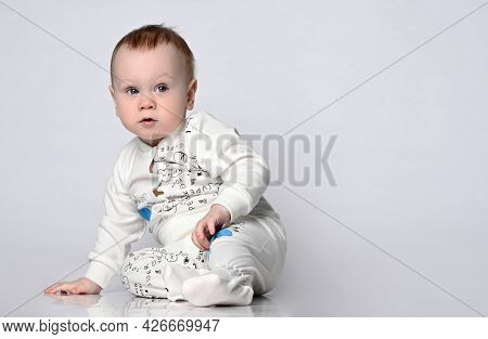 Pensive Blue-eyed Baby 11 Months Old Sits On The Floor, Leaning On One Hand, He Is Dressed In A Ligh