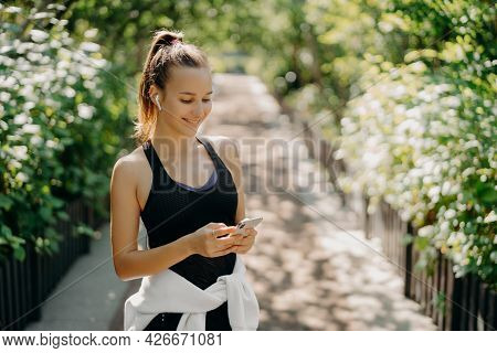 Sport As Style Of Life. Horizontal Shot Of Healthy Slim Sporty Woman Focused At Smartphone Checks In