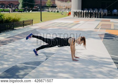 Sporty Slim Young Woman Does Planking Exercise Raises Leg Demonstrates Her Determination Wears Sport