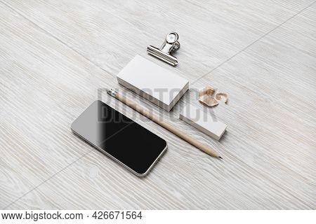 Blank Stationery Set On Light Wooden Background. Smartphone, Business Cards, Pencil And Eraser. Mock