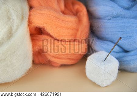 Needle In A Felted Cube And Skeins Of Wool On A Beige Background.