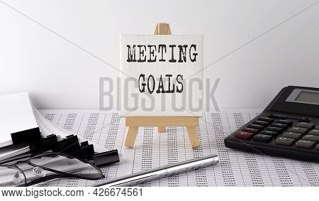 Text Meeting Goals On Easel With Office Tools And Paper.top View. Business
