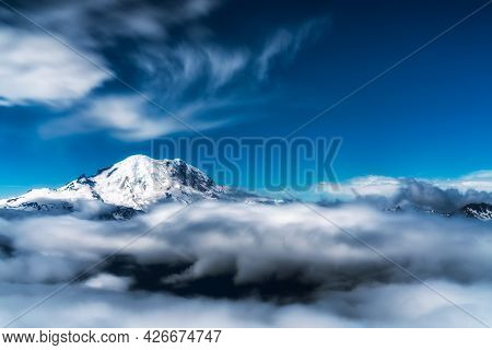 Mount Rainier In Washington Peaks Its Head Above The Wispy Clouds Below. Dramatic Rendition Of This