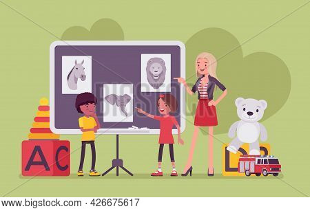 Kindergarten Lesson, Teacher And Children At Blackboard Studying Animals. Preschool Classroom, Eleme