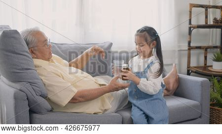 Asian Granddaughter Brought Medicine And Water For Grandpa To Eat On The Sofa In The Lounge, Senior