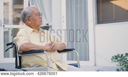 Disabled Senior Man Sitting On Wheelchair Alone In Rehabilitation Center, Portrait Happy Asian Gener