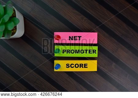 Net Promoter Score Write On Sticky Notes Isolated On Wooden Table.