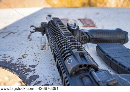Black Ar-15 And Rifle Gun On Top Of A White Rusty Table