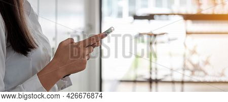 Businesswoman Using Her Smart Phone In Office. Female Entrepreneur Looking At Her Mobile Phone. Read