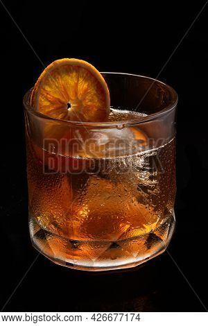 Misted glass of Alcoholic cocktail Old fashioned cocktail with orange slice, bourbon on black background. Copy Space