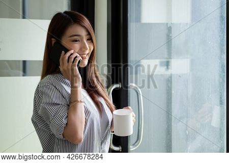 Smiling Asian Woman Talking On The Phone At Home, Happy Young Girl Holds Cellphone Making Answering