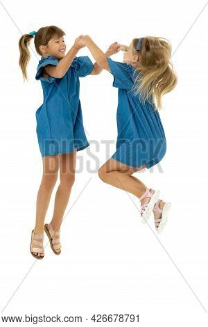 Two Happy Girls Jumping Holding Hands. Adorable Girls Sisters Dressed In The Same Denim Dresses And