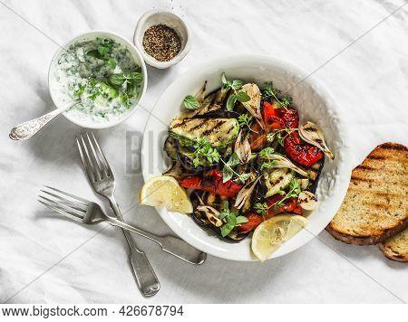 Grilled Vegetables Eggplant, Zucchini, Pepper Salad With Tzadziki Greek Yogurt Sauce On A Light Back