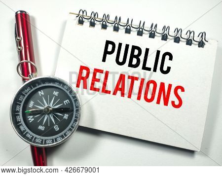 Business Concept.text Public Relations On Notebook With Compass And Pen On White Background.
