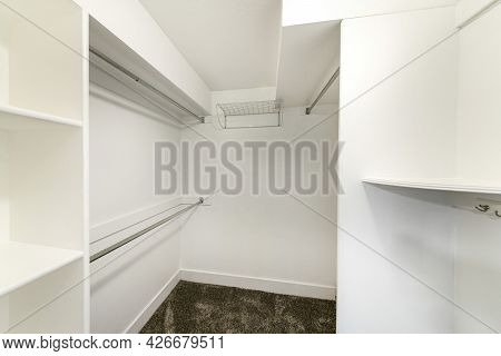 Interior Of A Plain White Walk In Closet With Shelvings And Carpeted Floor
