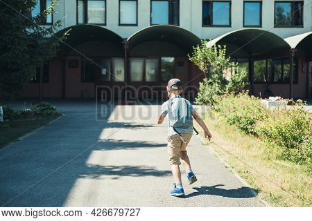 The Boy, Elementary School Student, Walking To School With Bag Behind Back And Book.  Students Are R