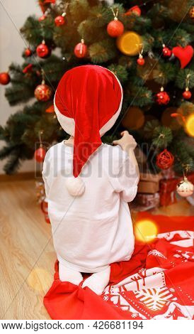 Cute Boy Indoors Near Xmas Tree Indoors. Christmas Eve Concept. Happy Child Decorating The Christmas