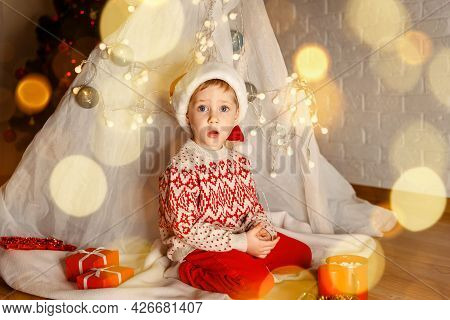 Cute Child Cheerful Mood Play Near Christmas Tree. It Is Miracle. Excited Kid Holding Present Near C