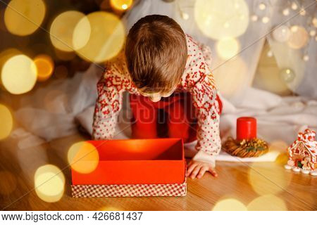Happy Little Boy With Xmas Gift Box. Child Playing Near Christmas Tree. Family With Gifts On Xmas Ev