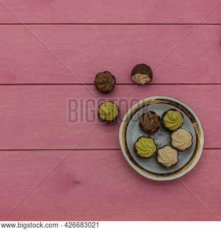 Chocolates With Praline, Pistachio, And Cream Filling Lie On A White Porcelain Saucer With A Gold Bo