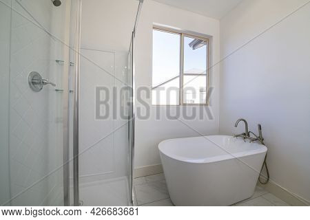 Freestanding Bathtub With Stainless Dual Faucet Fixture Against The Window