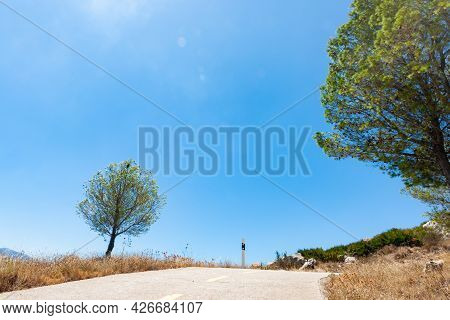 Road Through Coll De Rates Uphill Into Mountains With Dry Golden Grass Lining Road And Green Trees U