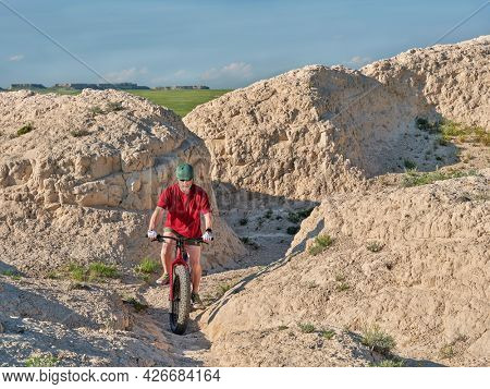 Senior male cyclist is riding a fat mountain bike along arroyo in badlands of Pawnee National Grassland in northern Colorado