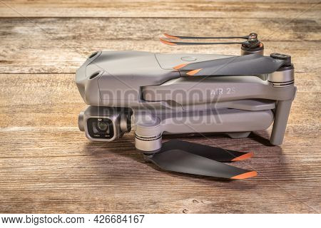 Fort Collins, CO, USA - July 4, 2021: DJI Mavic Air 2s drone in a folded position against rustic wood, an advanced prosumer folding drone.
