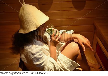 A Woman Drinks A Healthy Drink While Steaming In A Sauna. Beauty Therapy In The Spa. Health Care And