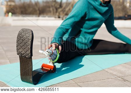 Young sportswoman with prosthesis doing exercise while working out on city bridge cropped