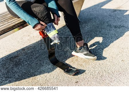 Cropped image of a young disabled sportswoman getting ready for workout wearing prosthetic leg sitting outdoors