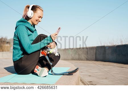 Young sportswoman in headphones with prosthesis sitting on a fitness mat using mobile phone outdoors