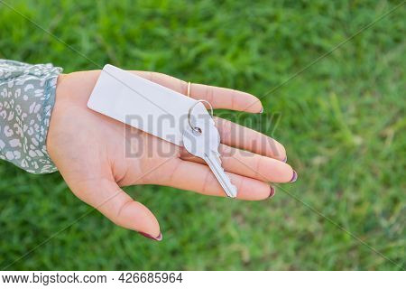 Woman Holding A Keyring With Green Grass Background.