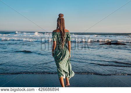 Backview Of Woman In Dress Against Seascape In Bali