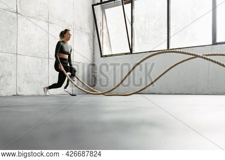 Young sportswoman with prosthesis working out with battle ropes indoors