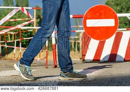 a pedestrian walks along a pedestrian crossing next to the road sign - traffic is prohibited and road works, the road is closed for maintenance