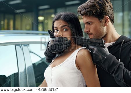 Angry robber closing mouth and threatening with pistol to scared girl. European man and young brunette woman stand near automobile. Male bandit wear hoodie. Concept of robbery and kidnapping