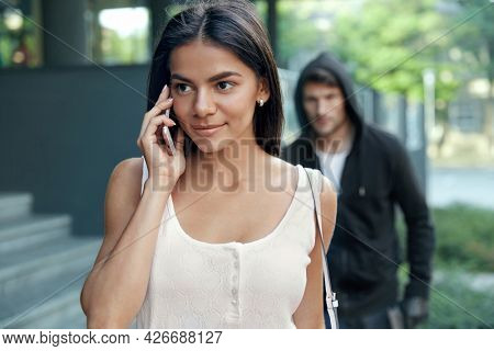 European girl talking on mobile phone. Robber sneaking behind woman. Young smiling brunette lady wear white dress. Male bandit wear black hoodie. Concept of robbery and kidnapping. City daytime