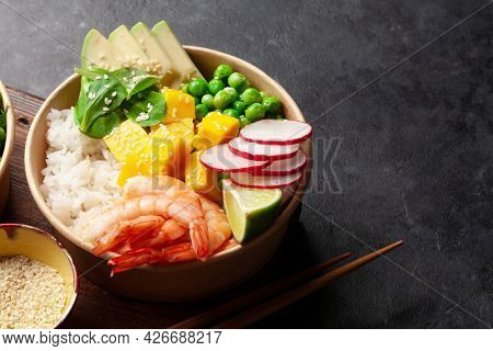 Poke bowl with shrimps, avocado and mango. Traditional hawaiian meal. With copy space