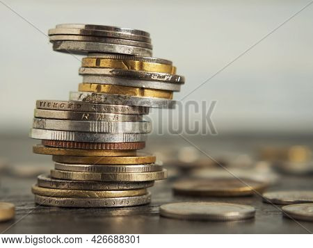 The Coins Of Different Countries Are Stacked On Top Of Each Other In Different Positions. On A Black