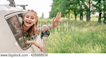 Beautiful preteen girl sitting in the car and looking out the window open and smiling. Happy child kid in the vehicle outdoors in the field during summer journey