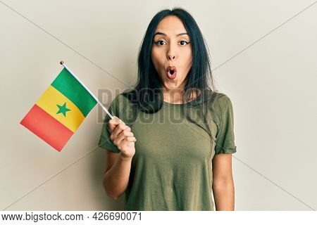 Young hispanic girl holding senegal flag scared and amazed with open mouth for surprise, disbelief face