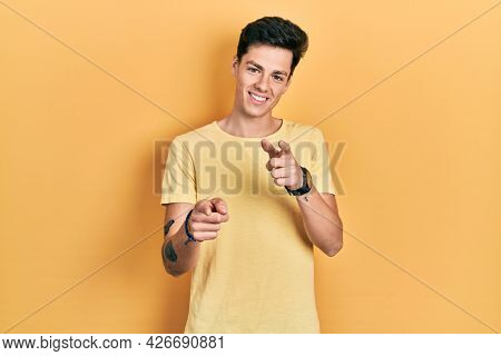 Young hispanic man wearing casual yellow t shirt pointing fingers to camera with happy and funny face. good energy and vibes.