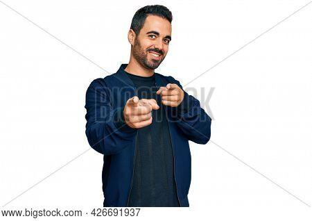 Young hispanic man wearing casual clothes pointing fingers to camera with happy and funny face. good energy and vibes.