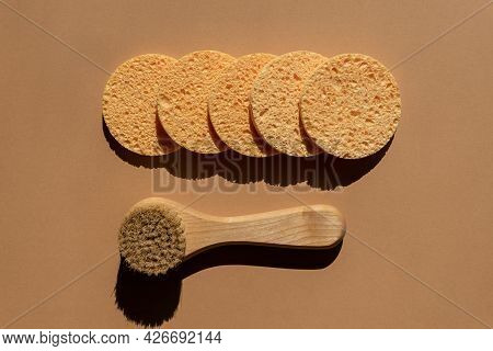 Shower Accessories - Face Brush With Natural Bristle And Round Cellulose Sponges On A Brown Backgrou