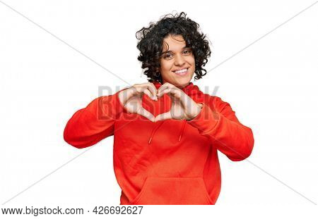 Young hispanic woman with curly hair wearing casual sweatshirt smiling in love showing heart symbol and shape with hands. romantic concept.